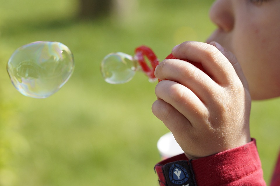 child blowing bubbles at a field